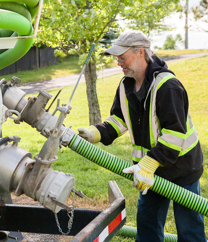 Man attaching hose to septic truck